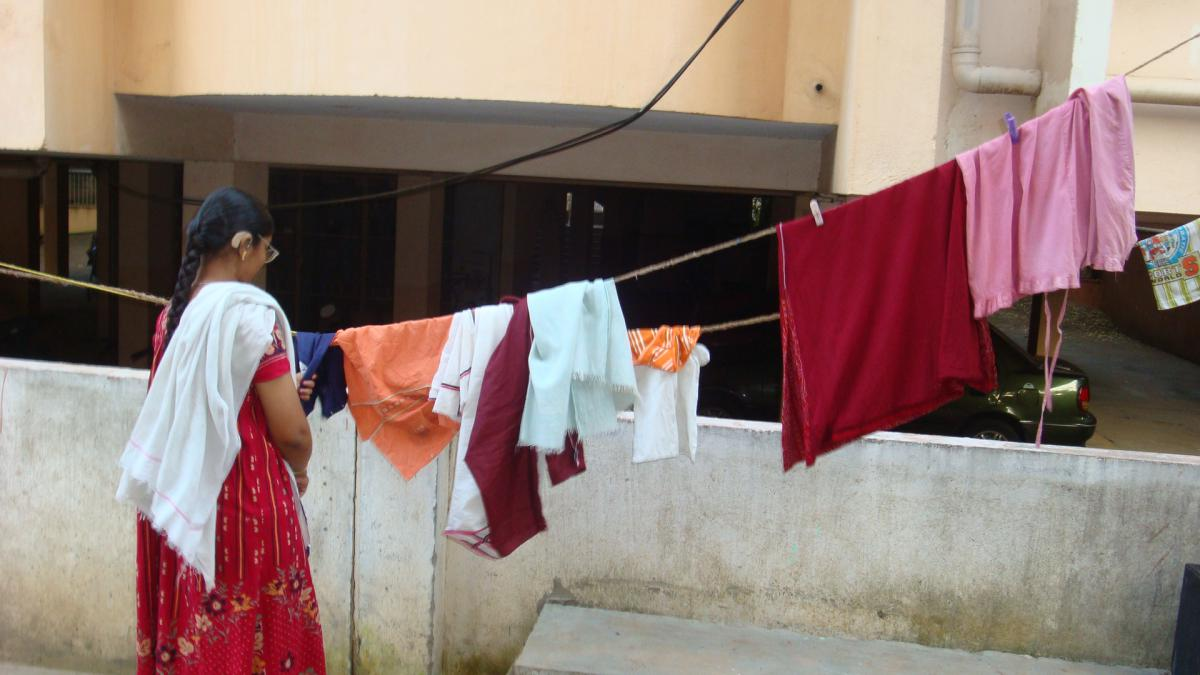 Photo of Sathiya hanging clothes on a line to dry.