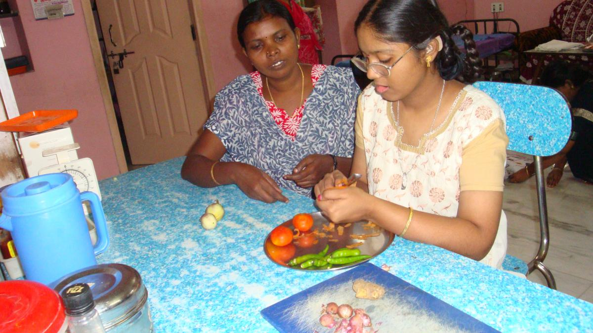 Sathiya peel vegetables as her teacher looks on.