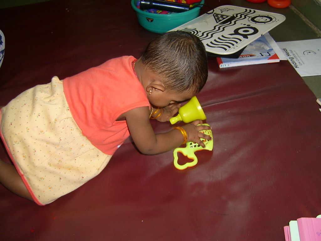 Girl crawling on mat and grasping toy