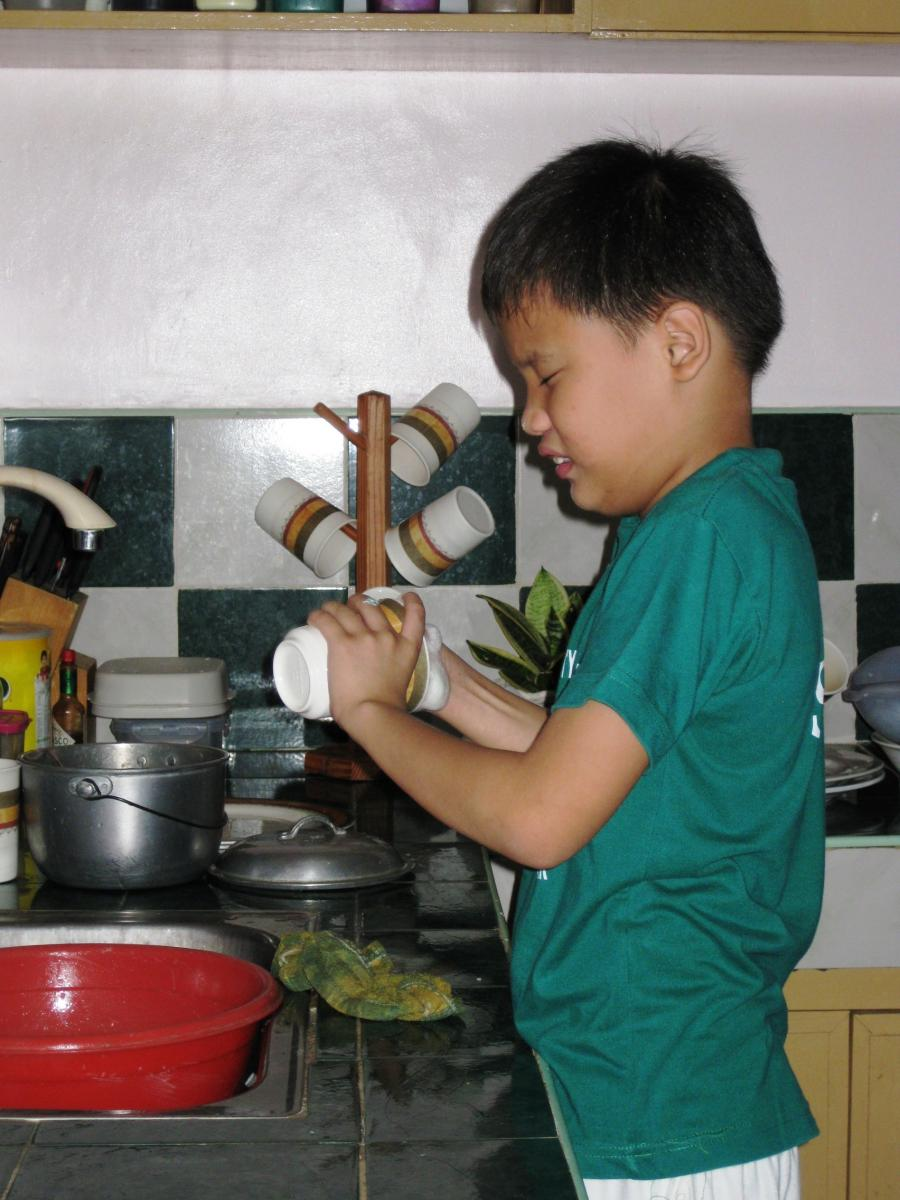 Boy washes dishes at the kitchen sink