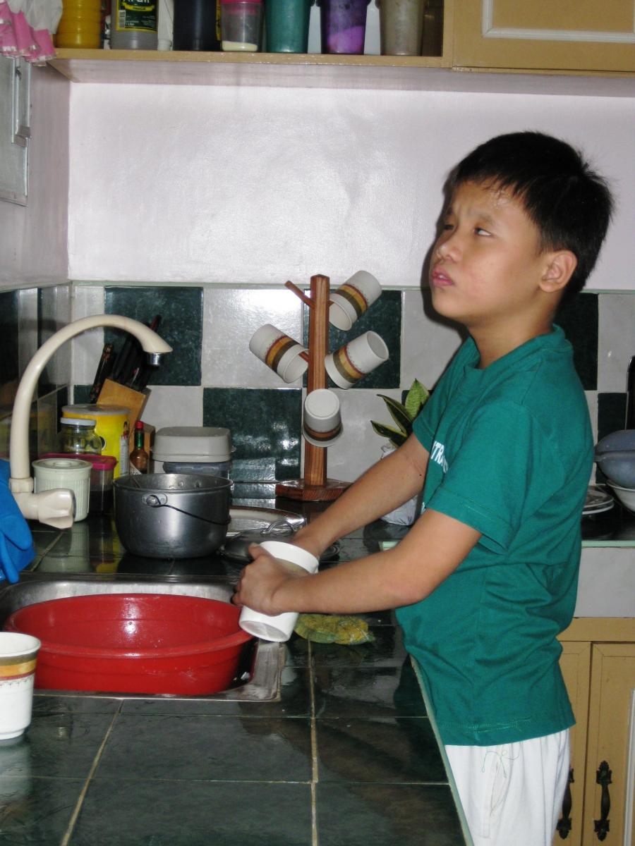 A boy washes thoroughly the inside of a cup.