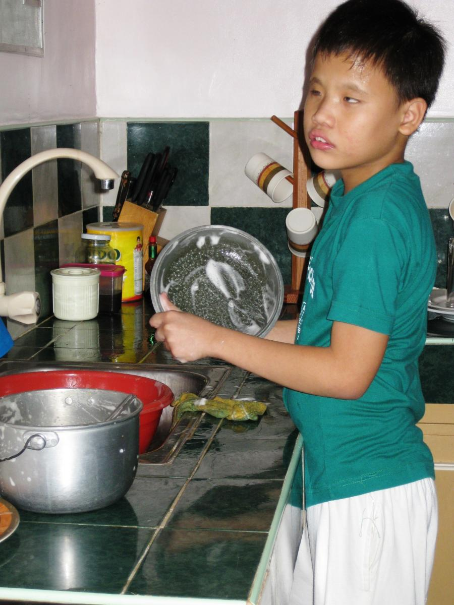 A boy washes a bowl at the kitchen sink.