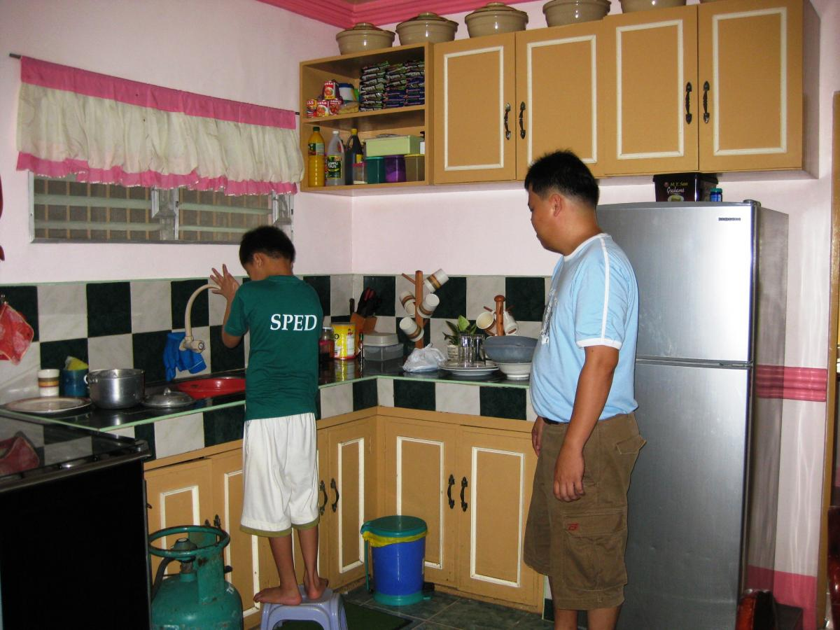 A father supervises his son doing the washing up
