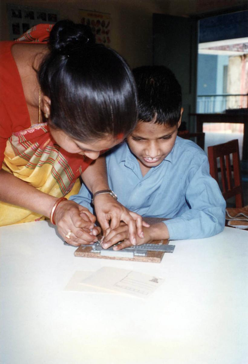 The teacher works with a boy to compose a letter to his family using a slate and stylus.