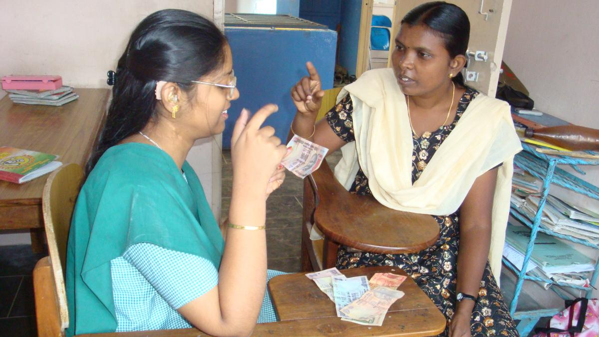 Sathiya works with her teacher to identify money.
