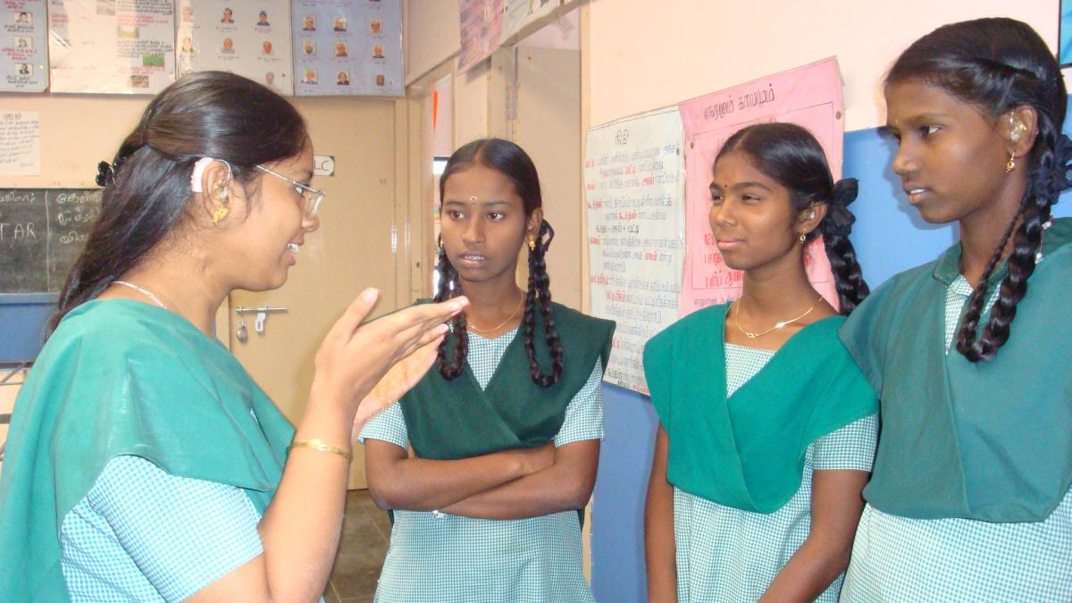 Sathiya uses sign language to communicate with her classmates.