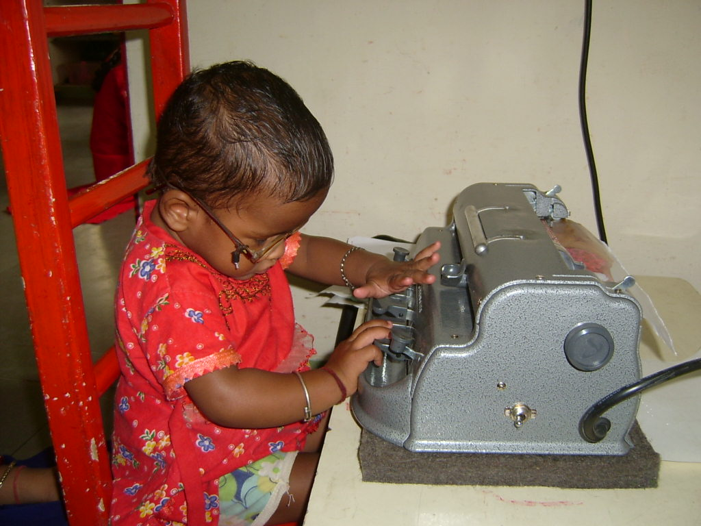 A young child with glasses uses a braille writer
