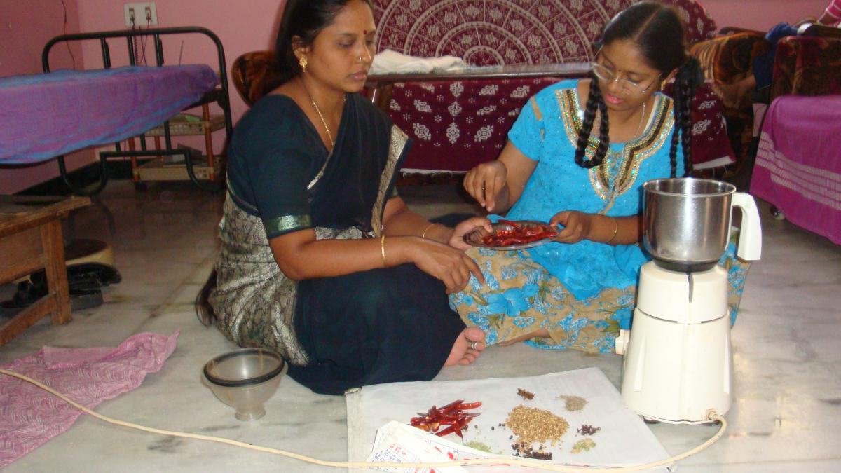 Sathiya works with her mother to measure out chilis and other ingredients for making curry powder.