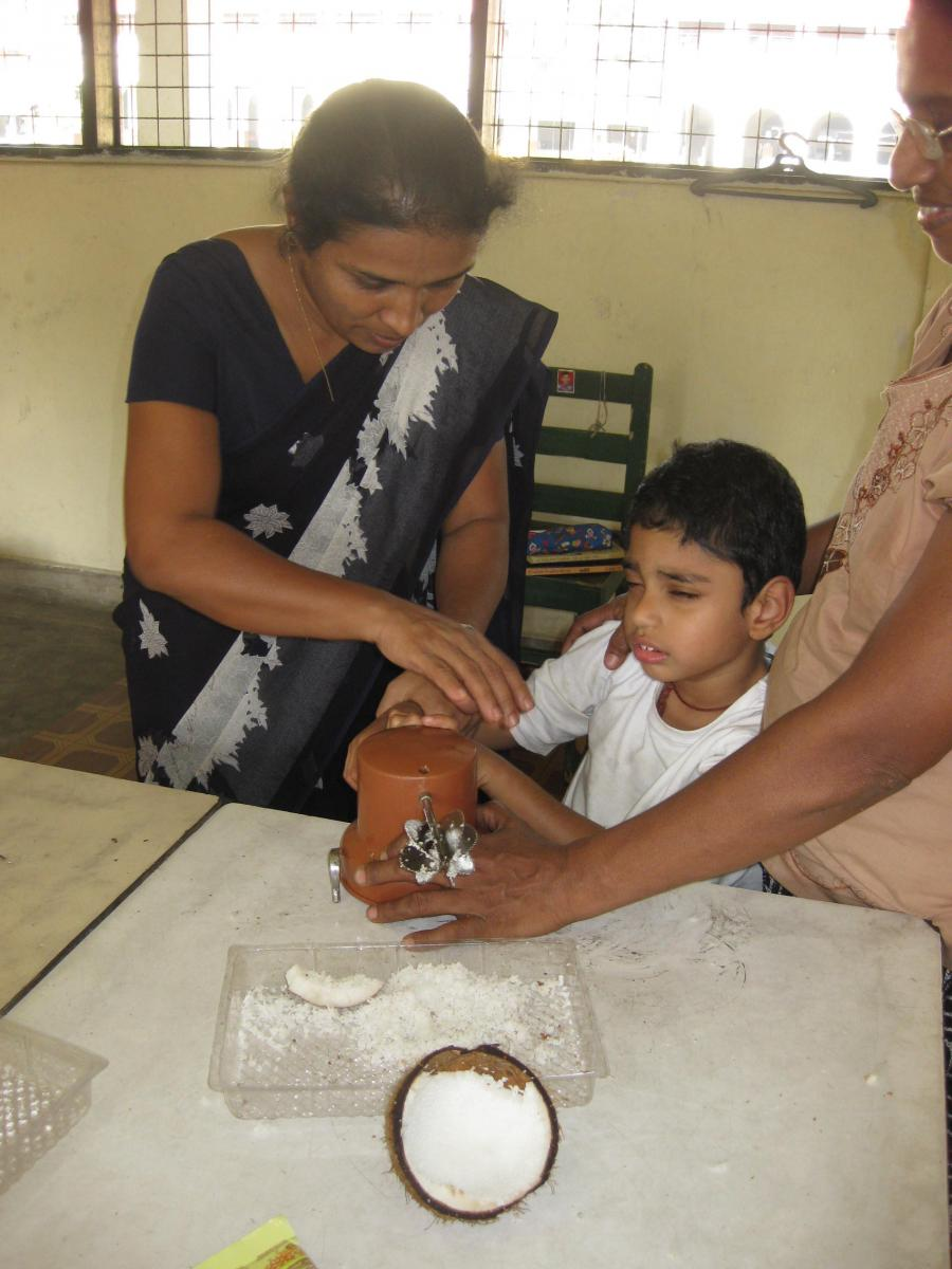A boy grates coconut