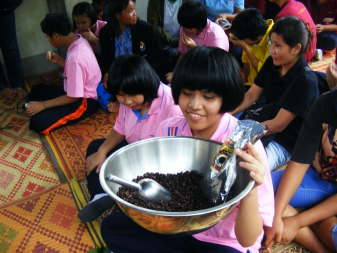a girl holds a bowl of coffee beans