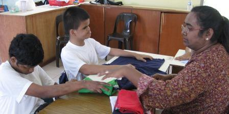 Two young men fold clothes with their teacher