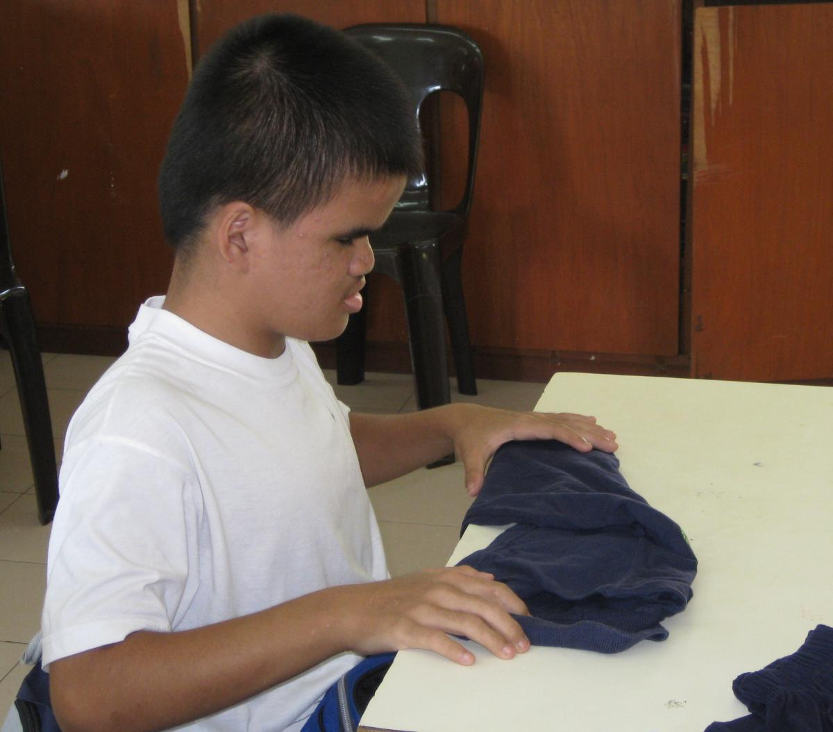 Young man folds laundry