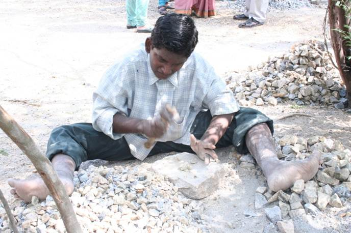 A young man makes gravel by hand.