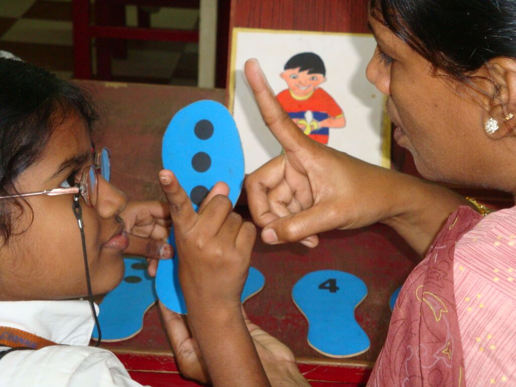 A girl with glasses holds up a finger to count
