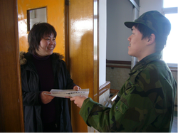 A students sells newspapers door to door