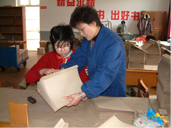 A student and teacher bind braille books