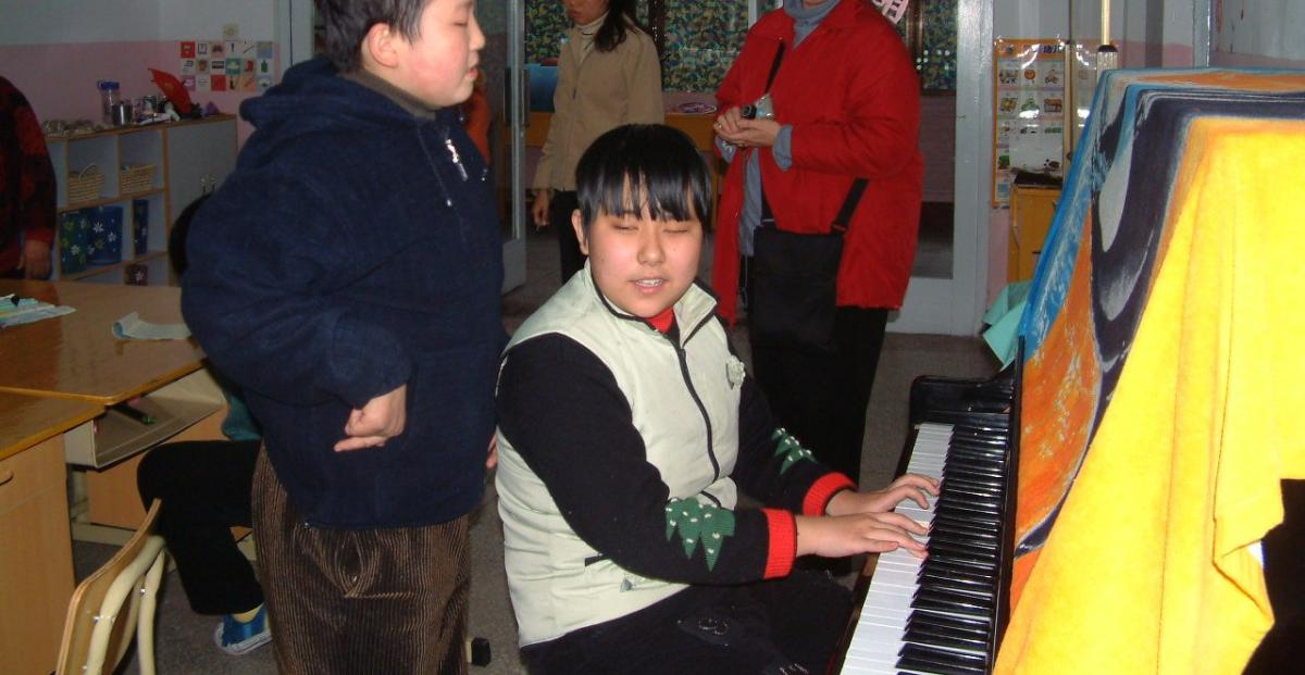 Nana plays the piano while a classmate sings