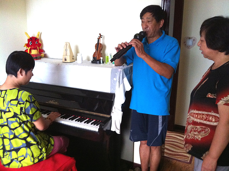 Nana plays the piano while her father plays a wind instrument.