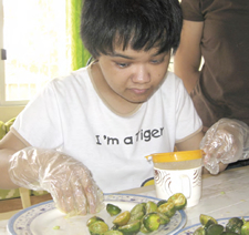 Photo of  a young woman placing portions of food on a plate as part of a lesson in food-service skills in the Philippines