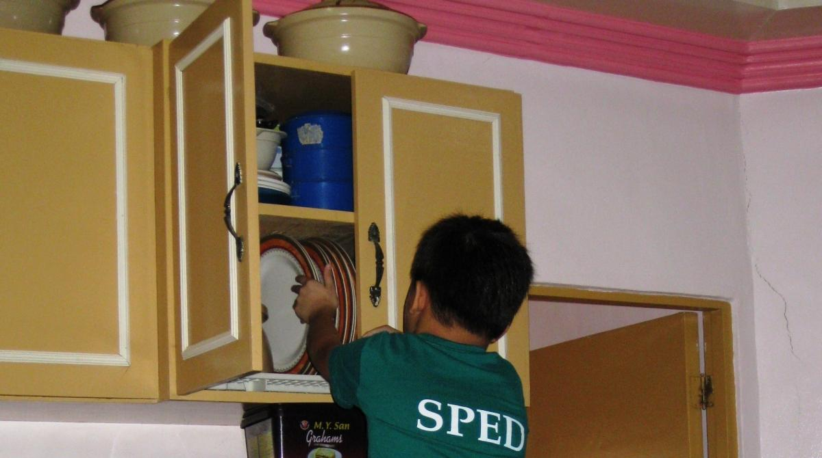 A boy puts away plates in a cabinet.