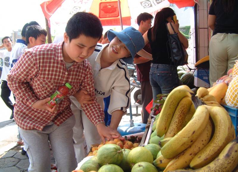 A student learns to select fruit at the market.