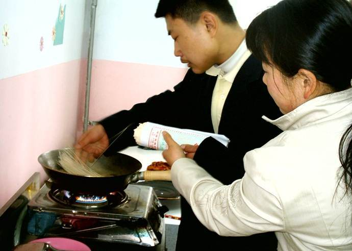 A student learns to cook using a gas stove.
