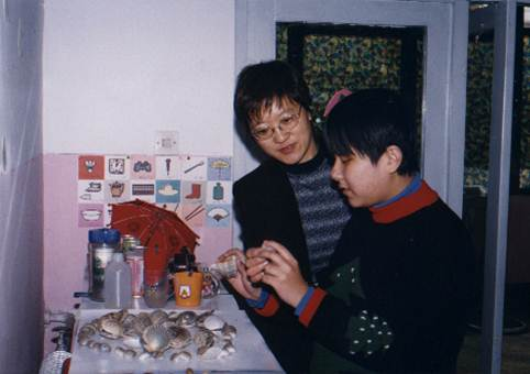 A student examines seashells as her instructor looks on.