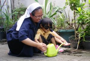 A young child helps to water the plants
