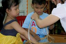 Two children reach in a basket