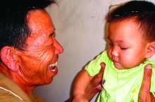 A man smiles at a young child