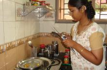 A young woman with a combined vision and hearing loss washes dishes.