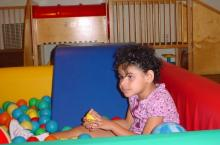 A young girl sits on a mat with small therapy balls