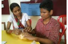 A boy seated at a table works with his teacher.