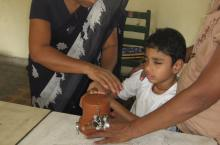 A boy helps to grate the coconut