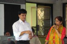 Photo of Pradip signing while woman with microphone interprets