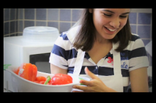 Young woman washes vegetables in the kitchen