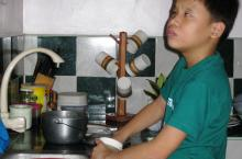 A boy washes dishes at the sink.