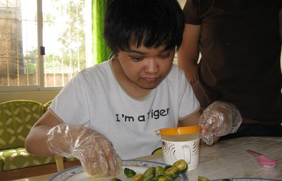 Photo of young woman wearing plastic gloves placing food on plate