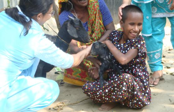 Photo of girl smiling and petting a goat while two adult women look on