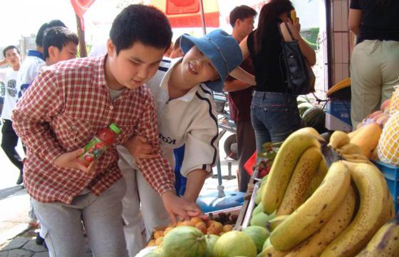 Photo of boy and teacher examining fruit in an outdoor market
