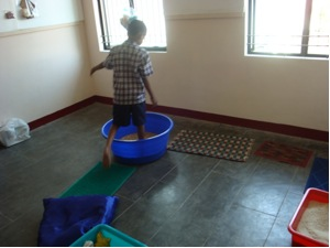 child walking into a blue tactile tub