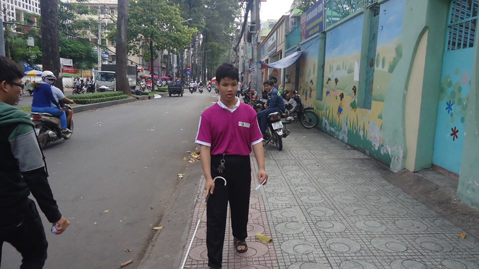 Teenage boy uses cane to travel on city sidewalk