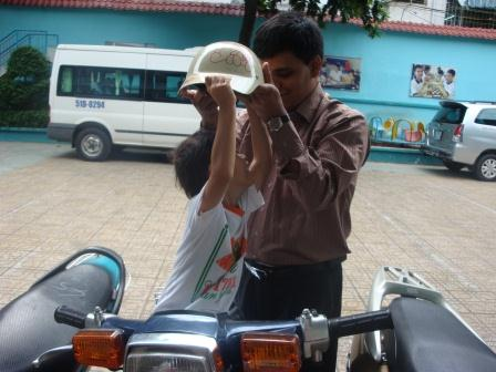 Photo of Pradip helping young boy put hard hat on his head