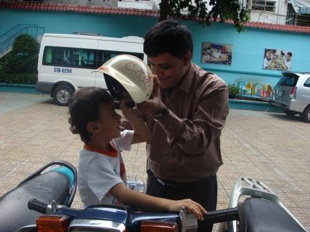 Photo of Pradip helping young boy put on hat