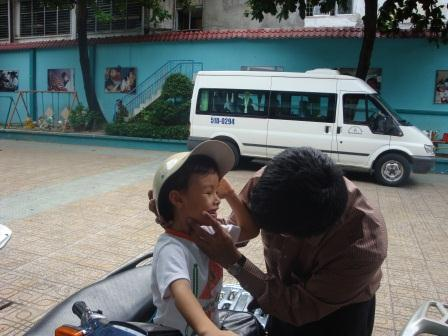 Photo of Pradip helping young boy put hat on his head