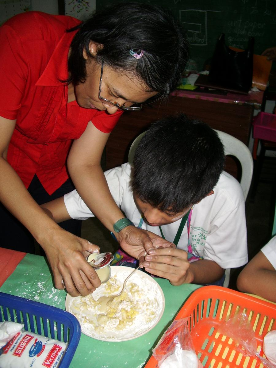 A boy spoons the condensed milk into the batter with the help of his teacher.