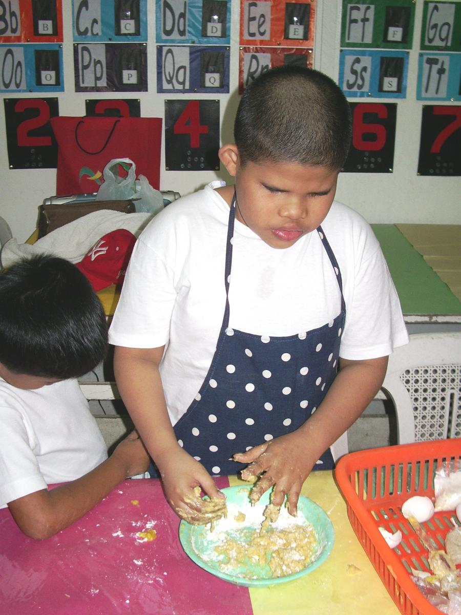 A boy mixes the dough with his fingers.