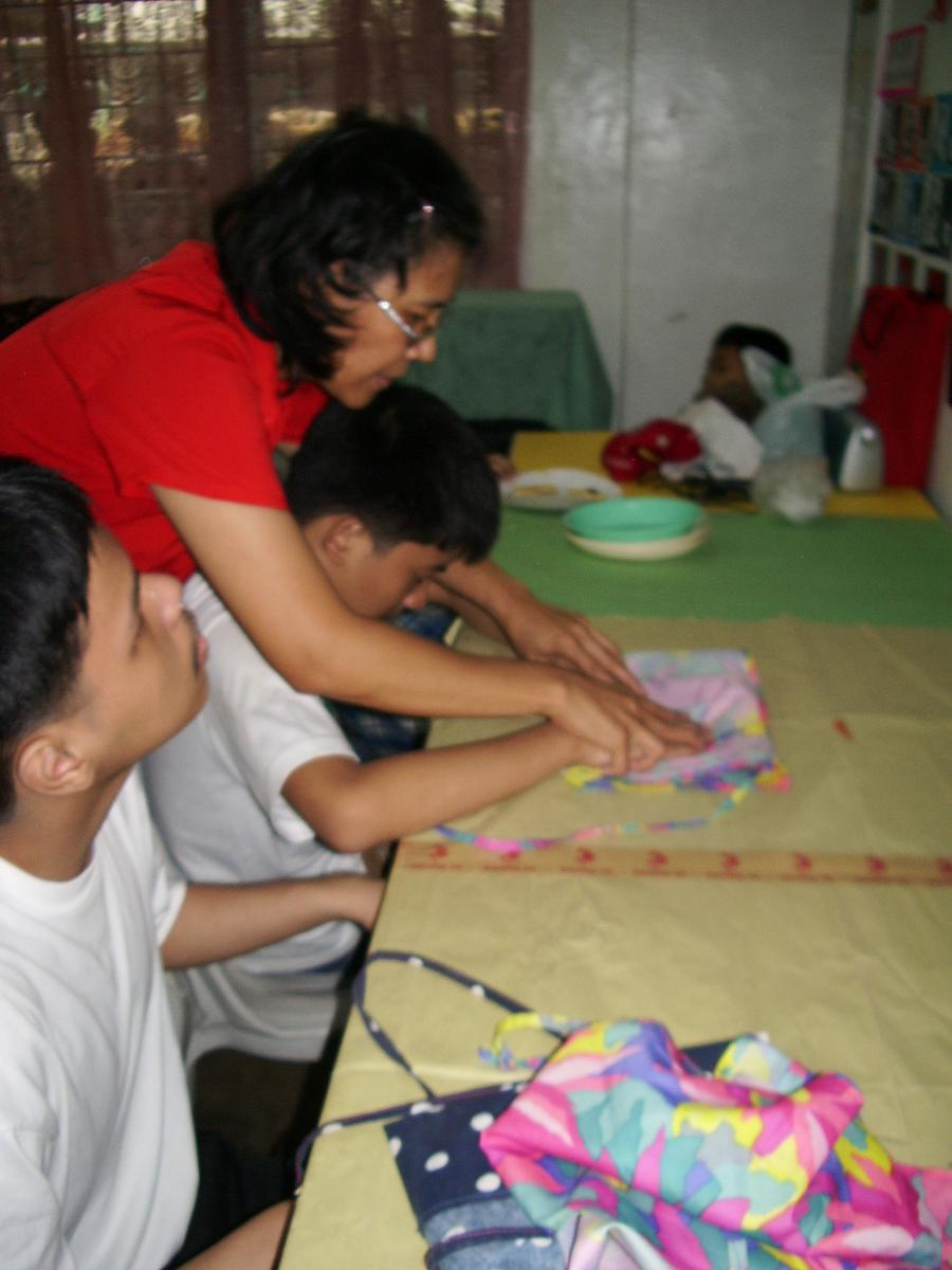 The teacher helps a boy to fold his apron after the activity has been completed.