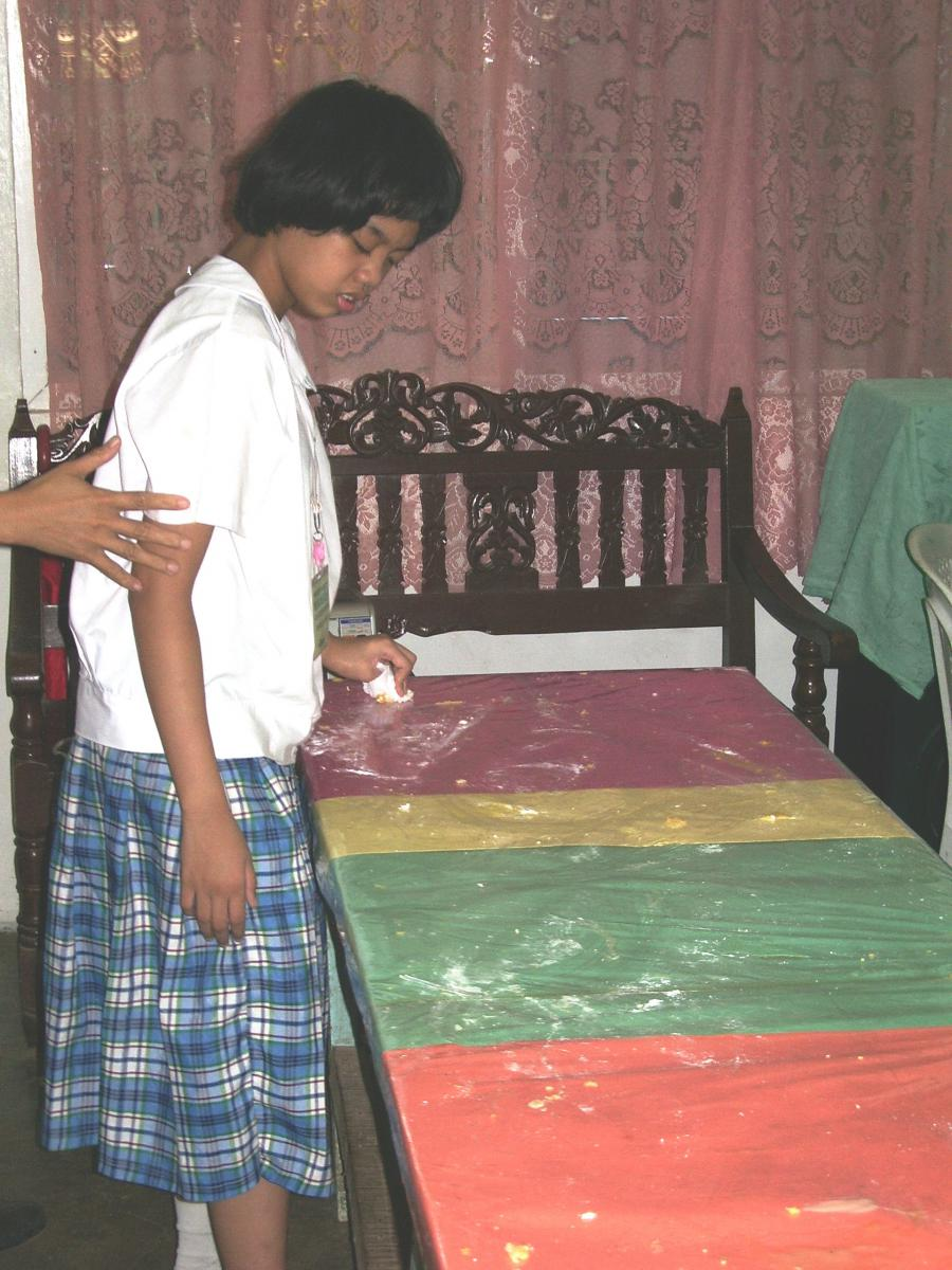 A girl wipes the table at the end of activity.