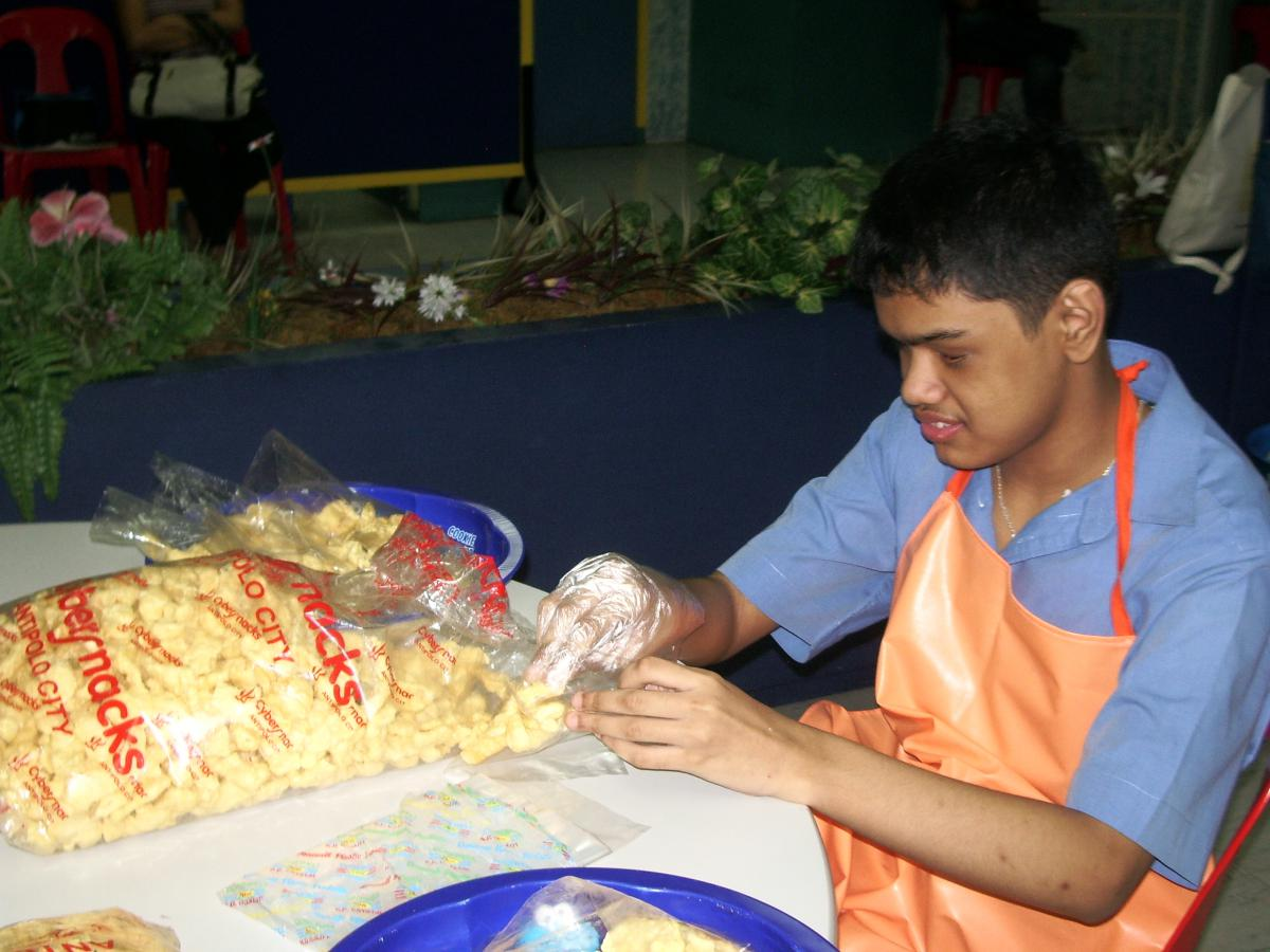 A boy places snacks into individual plastic bags.